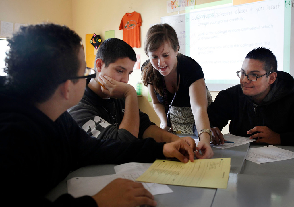 . College Readiness instructor Kate Perri helps students (l-r) Angel Garcia, Ezequil Ponce and Cristian Alonso fill out forms during a fifth period class at ACE Charter High School in San Jose, Calif. on Wednesday, Dec. 05, 2012. The class was later dropped from the curriculum. (Karl Mondon/Staff)