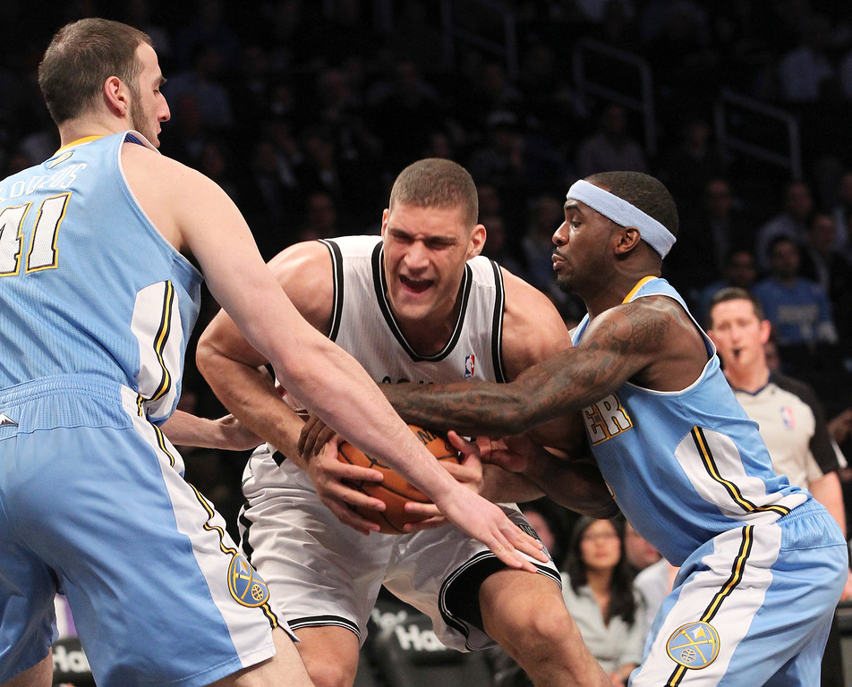 . Brooklyn Nets\' Brook Lopez, center, fights for a loose ball against Denver Nuggets\' Kosta Koufos, left, and Ty Lawson during the first half of an NBA basketball game of Wednesday, Feb. 13, 2013, at Barclays Center in New York.  (AP Photo/Mary Altaffer)