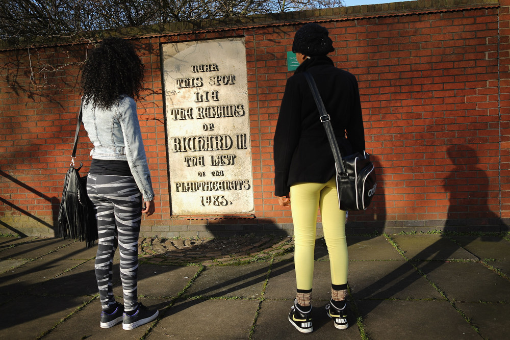 . LEICESTER, ENGLAND - FEBRUARY 04:  Students read a stone plaque incorrectly claiming to mark the spot where the remains of King Richard III lie near Leicester Cathedral, on February 4, 2013 in Leicester, England. The University of Leicester has been carrying out scientific investigations on remains found in a car park to find out whether they are those of King Richard III since last September, when the skeleton was discovered in the foundations of Grey friars Church, Leicester. King\'s Richard III\'s remains are to be re-interred at Leicester Catherdral.  (Photo by Dan Kitwood/Getty Images)