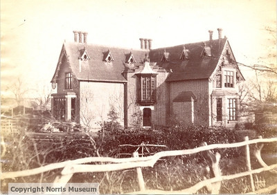 PH/SPALD/26: Spaldwick Vicarage:  a large house with tall chimneys and six dormer windows, decorated barge boards and large window over doorway.  Rough ground and rustic fencing in foreground.  Trees without leaf. Provided by the Norris Museum