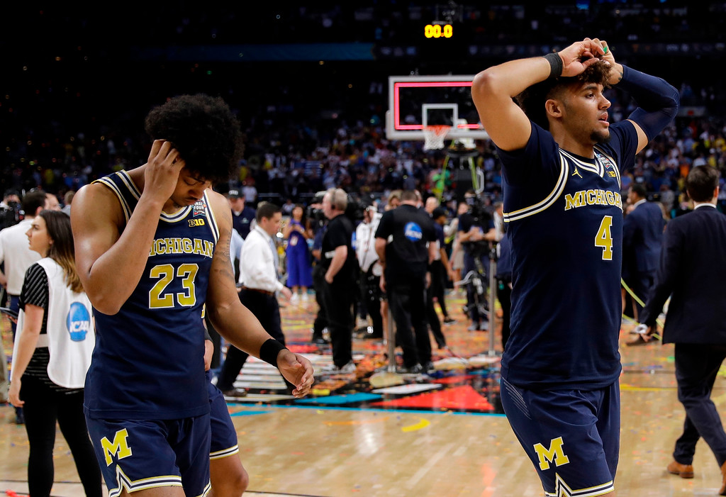 . Michigan\'s Ibi Watson (23) and Isaiah Livers (4) walk off the court after the championship game of the Final Four NCAA college basketball tournament against Michigan, Monday, April 2, 2018, in San Antonio. Villanova won 79-62. (AP Photo/David J. Phillip)
