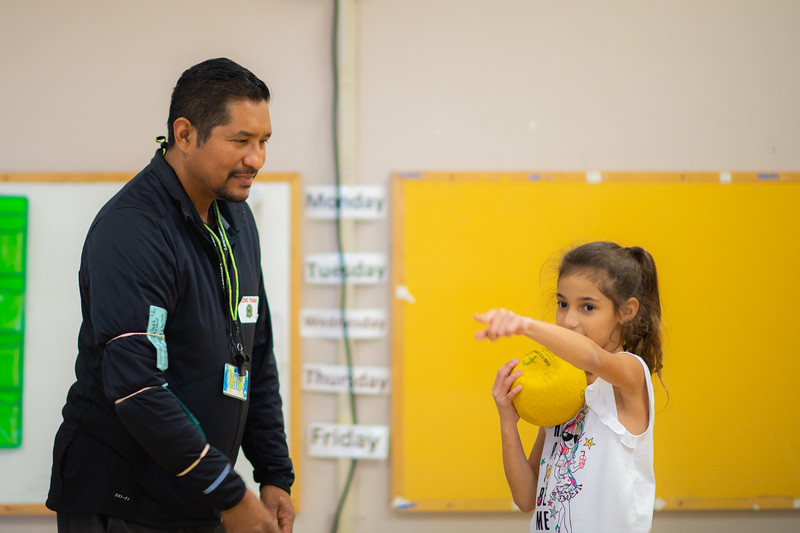 Luis Garcia gives instruction to elementary students on how to properly pass a ball.