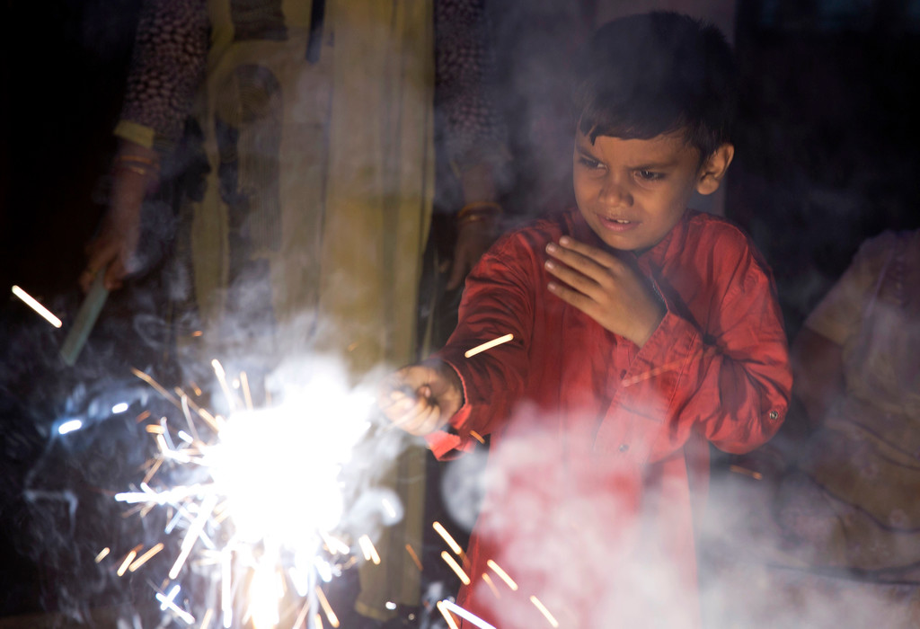 . An Indian boy plays with firecrackers to celebrate Diwali, the Hindu festival of lights, in Allahabad, India, Thursday, Oct. 19, 2017. Hindus light lamps, wear new clothes, exchange sweets and gifts and pray to goddess Lakshmi during Diwali, the festival of lights. (AP Photo/Rajesh Kumar Singh)