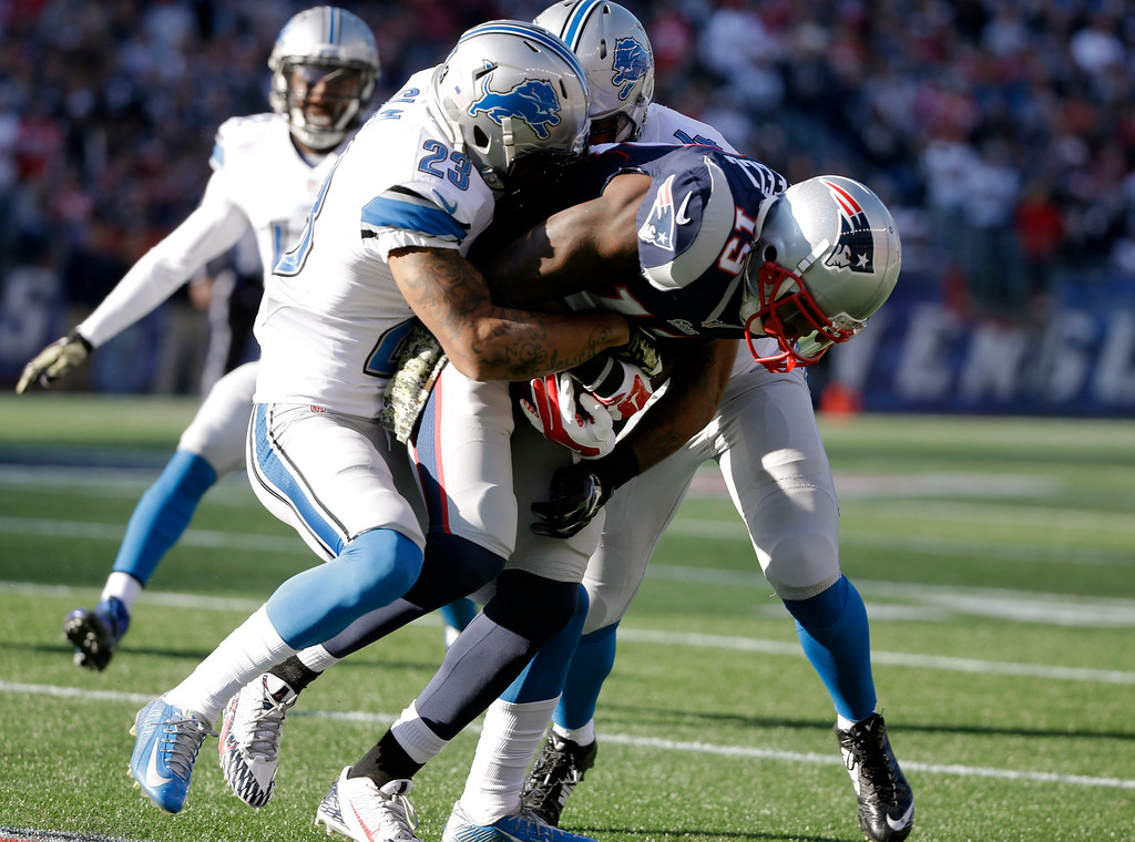 . Detroit Lions\' Darius Slay (23) and DeAndre Levy, rear, tackle New England Patriots wide receiver Brandon LaFell (19) in the first half of an NFL football game Sunday, Nov. 23, 2014, in Foxborough, Mass. (AP Photo/Steven Senne)