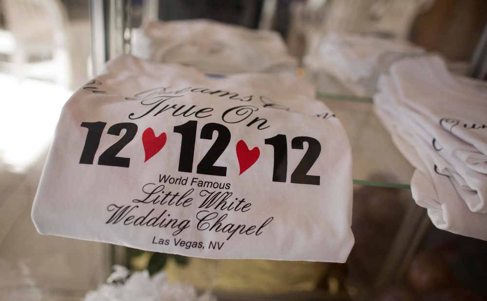 . Tee shirts advertising the 12-12-12 date sit on display at A Little White Wedding Chapel, Tuesday, Dec. 11, 2012, in Las Vegas. These ìonce-in-a-centuryî wedding dates have become more important each year as people increasingly look outside of Vegas for nontraditional wedding. Once known as the wedding capital of the world, Vegas\' share of the U.S. wedding market has fallen by a third since 2004.  Tuesday, Dec. 11, 2012, in Las Vegas. (AP Photo/Julie Jacobson)