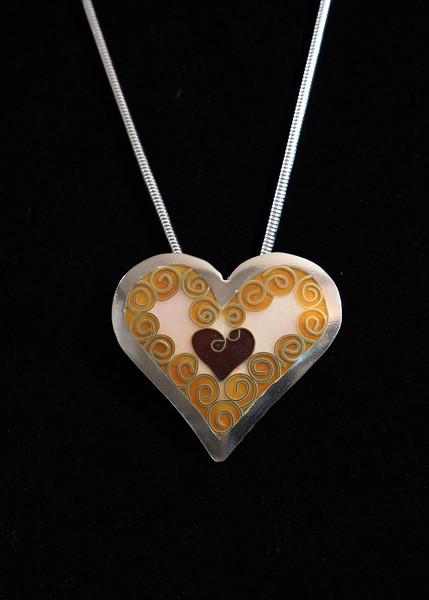 Fine Silver Champlevé and Cloisonné filigree heart with opalescent pink background. Pendant measures approximately 1 1/2 x 1 1/2 inches. Supported on a 16 inch Sterling silver snake chain. 175.00