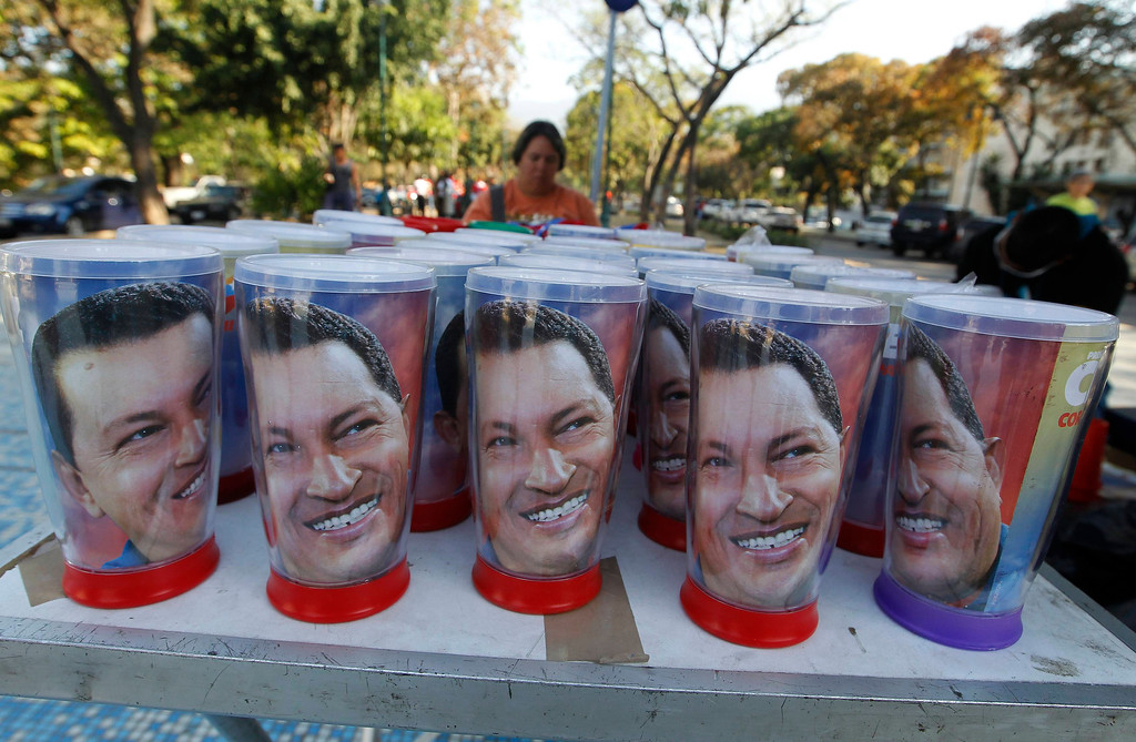 . Souvenir mugs of Venezuela\'s late President Hugo Chavez are offered for sale as thousands waited to view his body in state, at the military academy in Caracas March 8, 2013.     REUTERS/Mariana Bazo