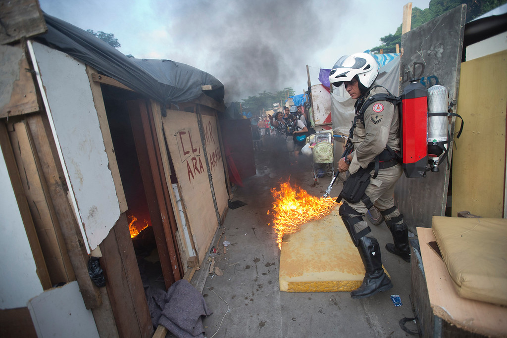 . A firefighter enters an area occupied by squatters during an eviction in Rio de Janeiro, Brazil, Friday, April 11, 2014. Squatters in Rio de Janeiro are clashing with police after a Brazilian court ordered that 5,000 people be evicted from abandoned buildings of a telecommunications company. Officers have used tear gas and stun grenades to try to disperse the families. (AP Photo/Silvia Izquierdo)
