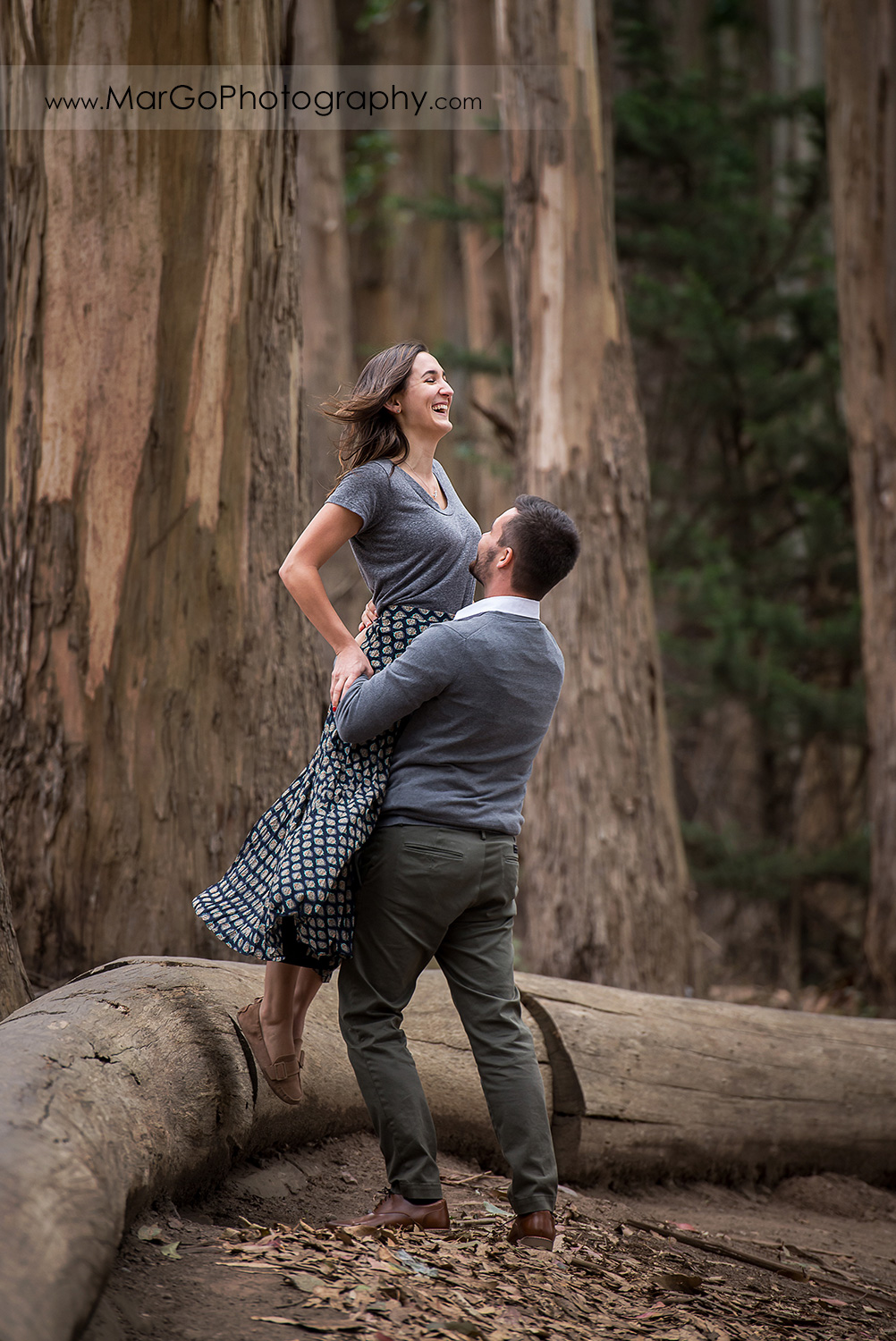 eengagement session at Lover's Lane at the Presidio in San Francisco - woman jumping into man's arms