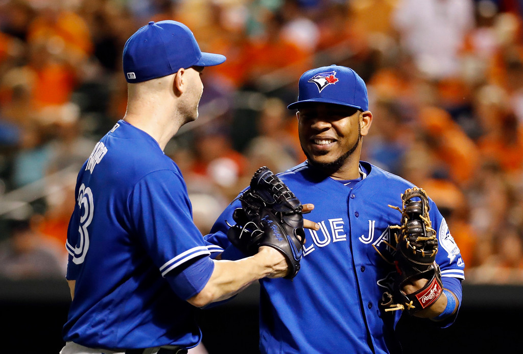 . Toronto Blue Jays starting pitcher J.A. Happ, left, and first baseman Edwin Encarnacion walk off the field after an inning of a baseball game against the Baltimore Orioles in Baltimore, Tuesday, Aug. 30, 2016. (AP Photo/Patrick Semansky)