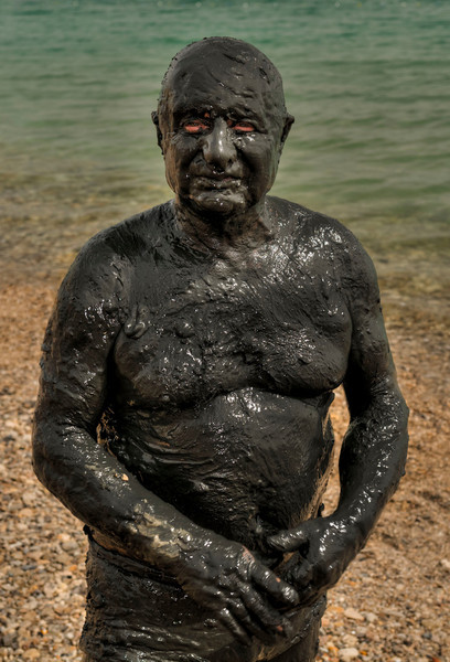 A polish man takes a mud bath in the dead sea.  The natural black mud is a mixture of many Dead Sea salts and minerals, rich in magnesium, natural tar (bitumen), and the silicates (silicon compounds), the organic elements from the shoreline all blended with earth. It is the silicates that have the effect of a mask to the skin and is useful for cleansing and softening the skin resulting in a wonderful glow. Generally, Dead Sea mud on the skin improves and stimulates blood circulation.   Dead Sea, Israel/Palestine, 2012.