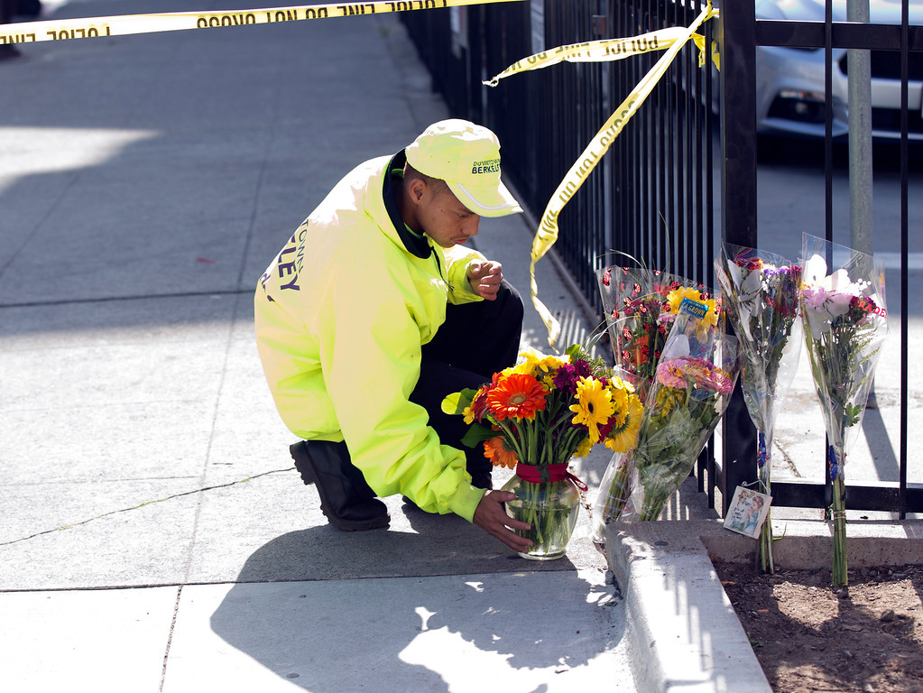 . An unidentified Downtown Berkeley Ambassador straightens flowers left at the scene on Kittredge Street where a balcony collapsed, sending 13 people plunging to the street below, Tuesday, June 16, 2015, in Berkeley, Calif. Six people were killed, and seven more were transported to area hospitals. (D. Ross Cameron/Bay Area News Group)