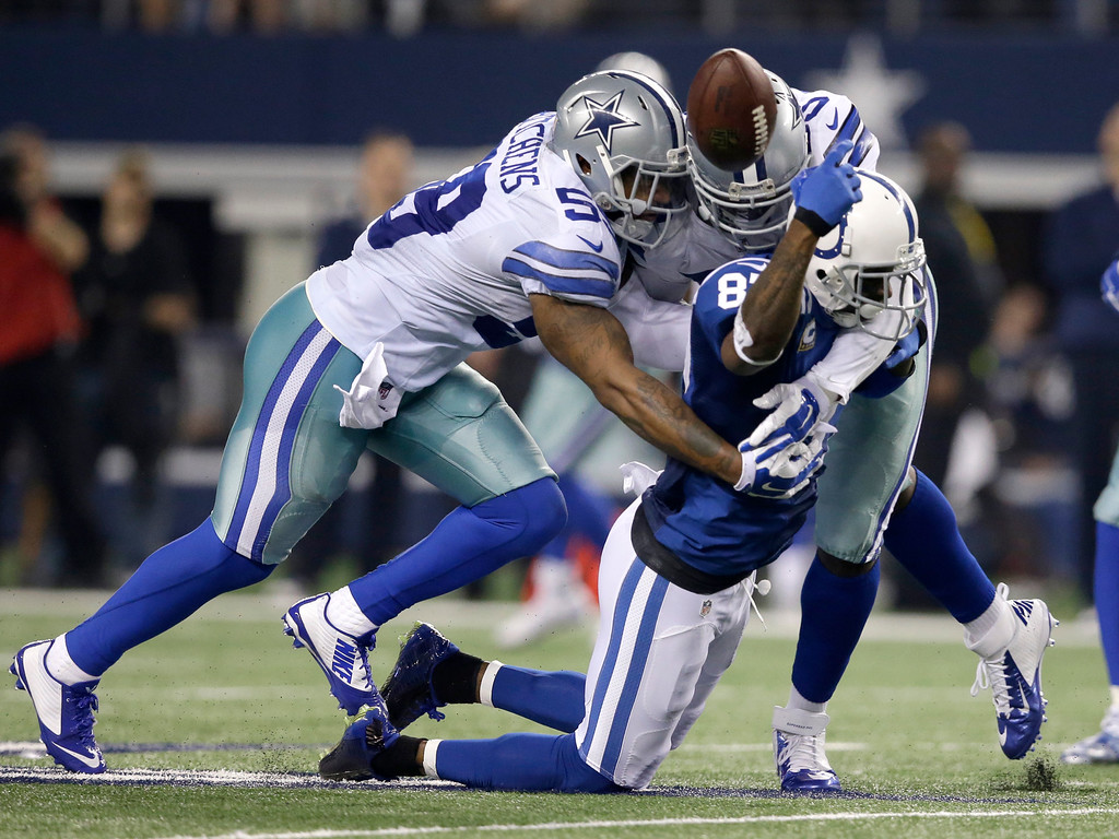 . Dallas Cowboys\' Anthony Hitchens (59), top left, and Rolando McClain, top right, break up a pass intended for Indianapolis Colts\' Reggie Wayne (87) during the second half of an NFL football game, Sunday, Dec. 21, 2014, in Arlington, Texas.(AP Photo/Tim Sharp)