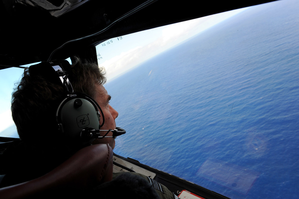 """. MALAYSIA AIRLINES FLIGHT 370:  The Australian Transport Safety Bureau (ATSB) has confirmed that missing Malaysia Airlines Flight MH370 is not in the search zone where acoustic pings were detected. The pings, originally believed to be coming from the missing jet, now thought to have been coming from a \'man-made source\', such as a searching ship or equipment used to detect pings. IN FLIGHT - APRIL 11: Co-pilot and Squadron Leader Brett McKenzie of the Royal New Zealand Airforce (RNZAF) P-3K2-Orion aircraft, helps to look for objects during the search for missing Malaysia Airlines flight MH370 in flight over the Indian Ocean on April 13, 2014 off the coast of Perth, Australia. Search and rescue officials in Australia are confident they know the approximate position of the black box recorders from missing Malaysia Airlines Flight MH370, Australian Prime Minister Tony Abbott said on Friday. At the same time, however, the head of the agency coordinating the search said that the latest \""""ping\"""" signal, which was captured by a listening device buoy on Thursday, was not related to the plane.  (Photo by Greg Wood - Pool/Getty Images)"""