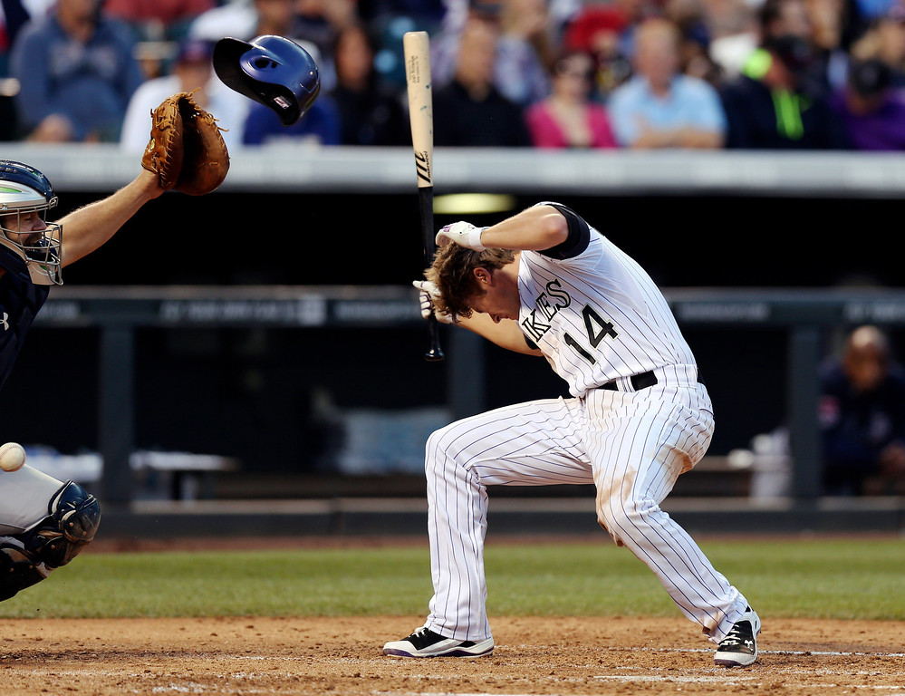 . Colorado Rockies\' Josh Rutledge, right, helmet is knocked off after getting hit by a pitch in the head as Atlanta Braves catcher Evan Gattis, left, fields the ball in the fifth inning of a baseball game in Denver on Wednesday, June 11, 2014. (AP Photo/David Zalubowski)