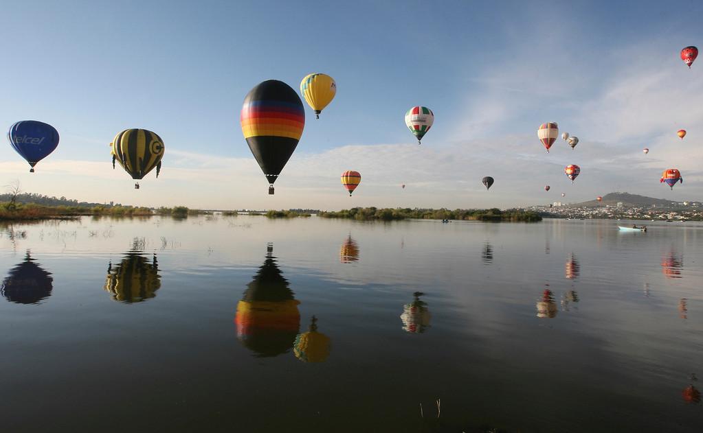 . Balloons take off over the Palote dam during the Hot Air Balloon Festival in Leon, Mexico, Friday, Nov. 15, 2013.  (AP Photo/ Mario Armas)