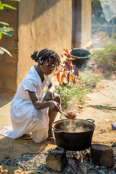 """Kapinga Alphoncine, 13 yr-old girl, cooking beans for dinner, and helping her grandmother weed their manioc (cCassava) garden.  She lives with her grandmother, Kapinga Godelive, 66 and her 3 brothers: 1-Francois Ngondo, 14 2-Mbuyamba Phillip, 9 3-Beya Honore, 6 Kananga, DRC Democratic Republic of Congo.  Hunger Their house is surrounded by garden on all sides. They grow cassava leaves, potato leaves (these are plants that just yield the leaves, not the roots that are the actual cassava and potatoes.)  Kapinga helps cook but only vegetables, beans and sometimes meat. Her granny makes the fufu a thick porridge-like food made from cassava flour and sometimes cornmeal. Fufu is a staple of Congolese diets. They only eat once a day, usually in the evening about 4 or 5.  Economic Development At the gardens around her home, Kapinga's grandmother grows cassava leaves, potato leaves, taro, sorrel and sugar cane. Grandmother also works a field away from the house. The veggies she grows she sells to buy cassava flour for the fufu.  She sells cassava leaves and sometimes would to get a little money but says they are suffering very much. She can get about 7,000 Congolese francs (about $4 dollars) for a full basin of cassava leaves.  When granny works the fields, Kapinga watches her brothers.   Inside Kapinga's four-room house the walls are paint splattered. There is little furniture except for two small tables and an old cabinet. On top sits a dusty old television. A peek behind reveals that it has no cord. Kapinga sits on a low, wooden bench against one wall reading an old school exercise book of English lessons. """"Good morning my friends, good morning.""""  Her English is good in spite of a mispronunciation here and there. High up on the wall to the right is a crucifix. It's as battle worn as the rest of the house. Light streams in through the numerous holes in the tin-sheeted roof. In the yard outside, the house is ringed on all sides with gardens of potato and cassava leaves, sor"""