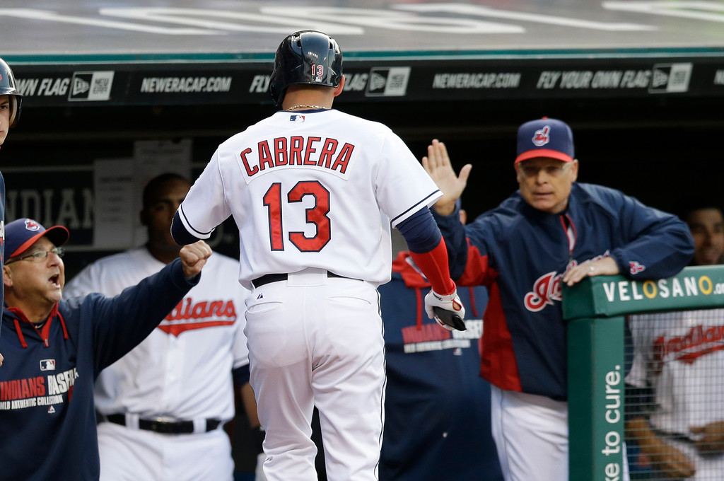 . Cleveland Indians\' Asdrubal Cabrera is congratulated by teammates after scoring on a wild pitch by Detroit Tigers starting pitcher Drew Smyly in the first inning of a baseball game, Monday, May 19, 2014, in Cleveland. (AP Photo/Tony Dejak)