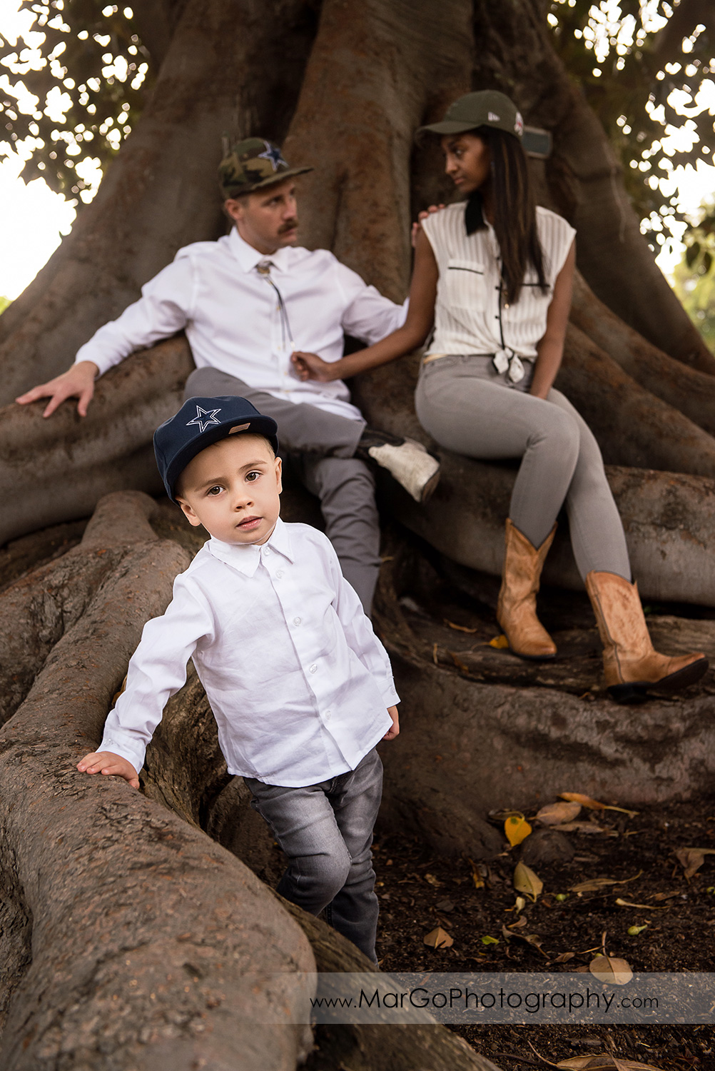 little boy in white shirt with man and woman in white shirt and gray jeans on a big tree in Shinn Historical Park and Arboretum in Fremont