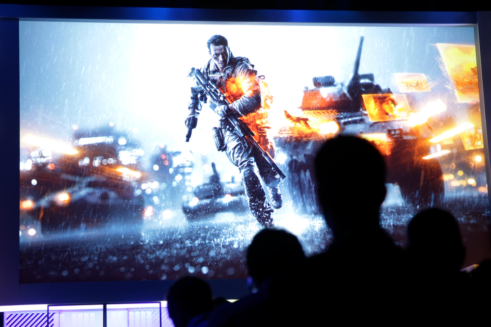 . Attendees watch a presentation on video game Battlefield 4 at the Microsoft Xbox E3 media briefing in Los Angeles, Monday, June 10, 2013. Microsoft focused on how cloud computing will make games for its next-generation Xbox One console more immersive during its Monday presentation at the Electronic Entertainment Expo. Microsoft announced last week that the console must be connected to the Internet every 24 hours to operate, and the system would ideally always be online. (AP Photo/Jae C. Hong)
