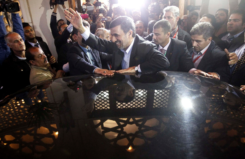 . Iran\'s President Mahmoud Ahmadinejad waves after visiting Sheikh Ahmed al-Tayeb, Egypt\'s leading Sunni Muslim scholar at the historic al-Azhar mosque and university, in Cairo February 5, 2013. Mahmoud Ahmadinejad was both kissed and scolded on Tuesday when he began the first visit to Egypt by an Iranian president since Tehran\'s 1979 Islamic revolution. The trip was meant to underline a thaw in relations since Egyptians elected an Islamist head of state, President Mohamed Mursi, last June. But it also highlighted deep theological and geopolitical differences.       REUTERS/Mohamed Abd El Ghany