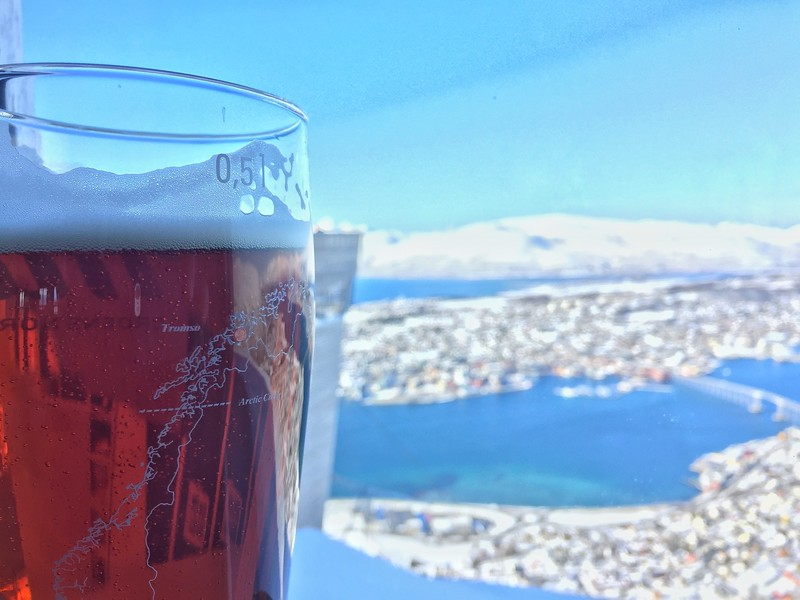 Drinking beer in winter at the top of mountain and looking over the city, Tromso, with the view cover with snow.