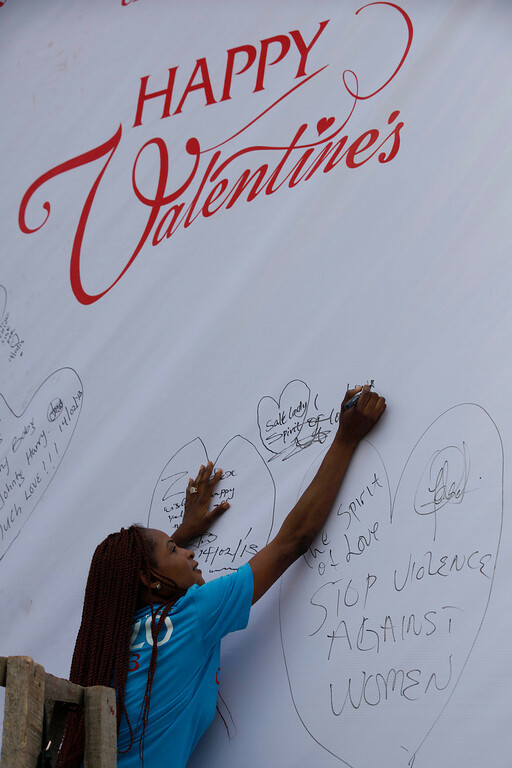 ". A student sign on a giant valentine card with inscriptions \'\' stop violence against women\'\' to support the ""One Billion Rising\"" global campaign in Lagos, Nigeria, Thursday, Feb. 14, 2013. Thousands of women and children in various cities in the country danced in the streets, in malls and other places to express support for the One Billion Rising movement, a worldwide call to end violence against women and girls. (AP Photo/Sunday Alamba)"