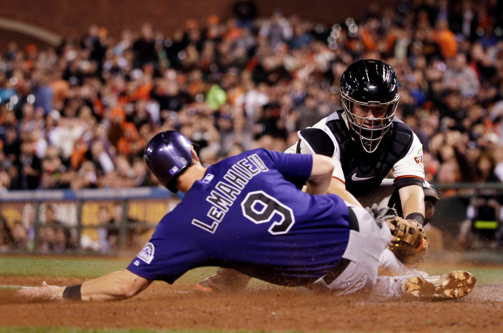 . Colorado Rockies\' D.J. LeMahieu (9) is tagged out at the plate by San Francisco Giants catcher Andrew Susac after a single by Charlie Blackmon during the seventh inning of a baseball game Monday, Aug. 25, 2014, in San Francisco. (AP Photo/Marcio Jose Sanchez)