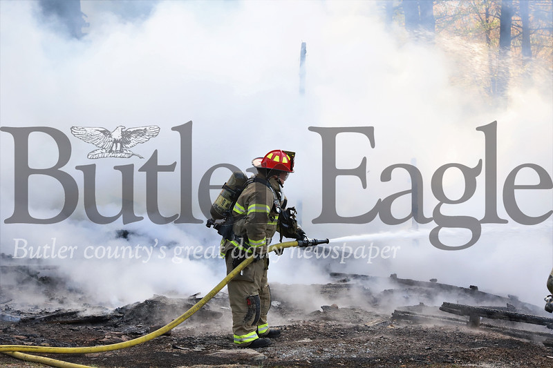 A firefighters douses remains of a structure fire on Little Creek Road Tuesday evening. Seb Foltz/Butler Eagle