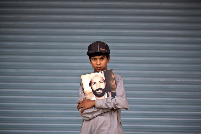 . Ali Haider, 10, poses for a portrait holding a photograph of his father, who went missing on July 14, 2010, while he and other relatives take a break from a long march protest, in Rawalpindi, Pakistan, Friday, Feb. 28, 2014. Ten-year-old Ali Haider has spent the last four months of his life walking across the breadth of Pakistan in an effort to find out what has happened to his father who has been missing since 2010. Haider is the youngest of two dozen activists from the impoverished southwestern province of Baluchistan who walked roughly 3,000 kilometers (1,860 miles) to the capital of Islamabad to draw attention to alleged abductions of their loved ones by the Pakistani government. (AP Photo/Muhammed Muheisen)