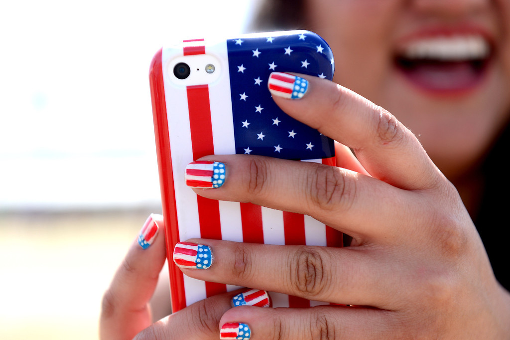 . A festival-goer uses her phone during the first day of Stagecoach Country Music Festival in Indio, Friday, April 25, 2014. The American flag is a common pattern worn at the festival. (Photo by Sarah Reingewirtz/Pasadena Star-News)