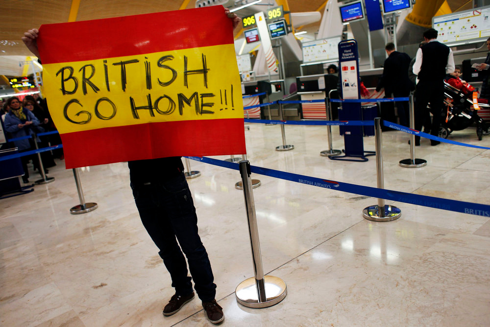 . An Iberia airline worker holds a Spanish flag next to British Airways and Iberia airline counters during a protest at Madrid\'s Barajas airport February 18, 2013. Striking union workers clashed with police at the airport on Monday on the first day of a week-long strike over more than 3,800 pending job cuts at Spain\'s flagship airline Iberia. REUTERS/Susana Vera