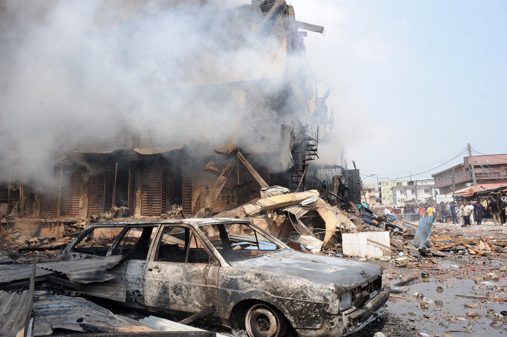 Description of . Burnt cars are seen after a strong explosion in a building in Lagos on December 26, 2012. Fire ripped through a crowded neighborhood in Nigeria's largest city and wounded at least 30 people after a huge explosion rocked a building believed to be storing fireworks, officials said. Fireworks continued to explode well after the fire began while smoke was heavy and the blaze intense, making it difficult for rescue workers and firefighters to approach the scene. AFP PHOTO/PIUS UTOMI EKPEI/AFP/Getty Images