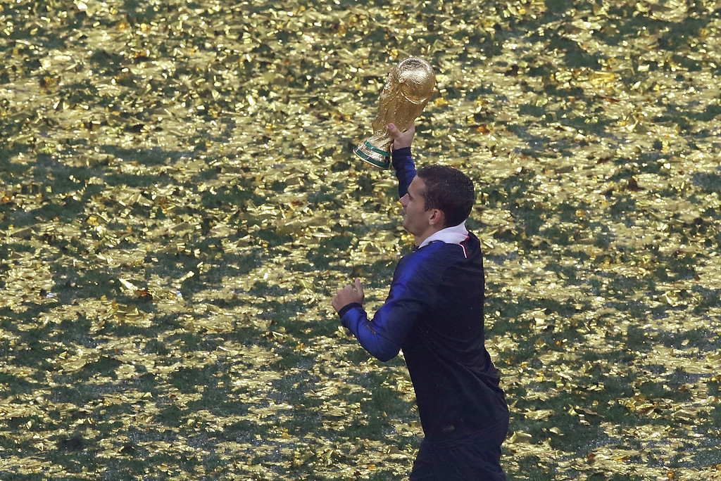 . France\'s Antoine Griezmann runs with the trophy at the end of the final match between France and Croatia at the 2018 soccer World Cup in the Luzhniki Stadium in Moscow, Russia, Sunday, July 15, 2018. (AP Photo/Thanassis Stavrakis)