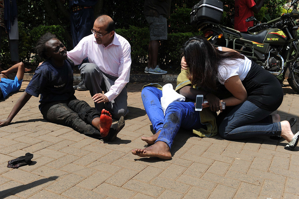. Injured people receive assistance from by passers after masked gunmen stormed an upmarket mall and sprayed gunfire on shoppers and staff, killing at least thirteen on September 21, 2013 in Nairobi.  AFP PHOTO/SIMON MAINA/AFP/Getty Images