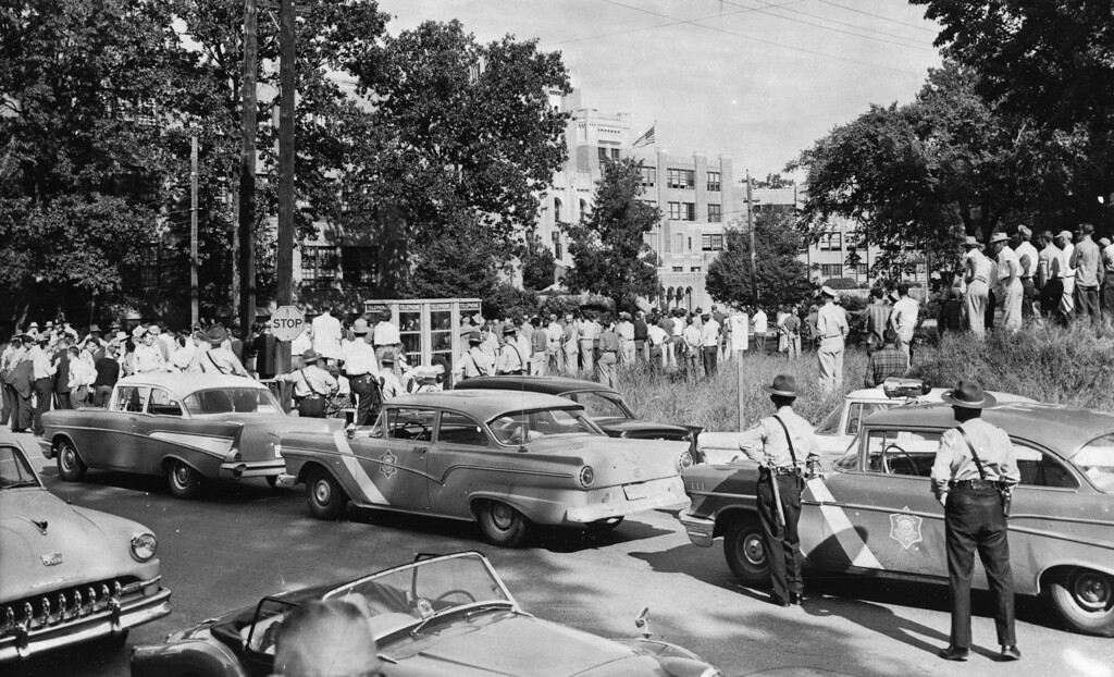 . This is the scene at Central High School in Little Rock, Ark., after the school was opened to all students, Sept. 23, 1957.  City and state police guard the school and a crowd of onlookers is kept back by barricades and police.  (AP Photo)