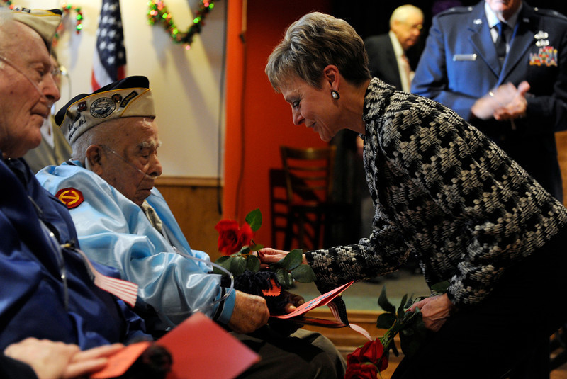 . Patricia Marnette, right, with the Sons and Daughters of Pearl Harbor Survivors, presents Luz Valerio and the rest of the veterans with a red rose. The American Legion Post 1 in Denver hosts a Remember Pearl Harbor 71st Anniversary Program on Friday, Dec. 7, 2012, honoring the survivors, their wives, and the widows. Kathryn Scott Osler, The Denver Post