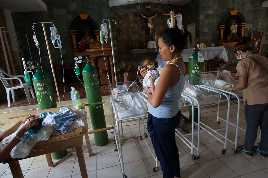 . Nanette Salutan holds her baby son Bernard in her arms in front of the altar of a Catholic chapel inside the Eastern Visayas Regional Medical Center in Tacloban, Philippines on Saturday Nov. 16, 2013. The chapel is now being used to care for infants after Typhoon Haiyan destroyed the original facility of the hospital. (AP Photo/David Guttenfelder)