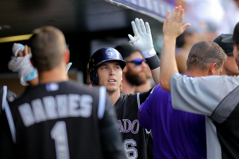 . Corey Dickerson #6 of the Colorado Rockies celebrates in the dugout after hitting a solo home run during the seventh inning against the Cincinnati Reds at Coors Field on August 17, 2014 in Denver, Colorado. The Rockies defeated the Reds 10-9. (Photo by Justin Edmonds/Getty Images)