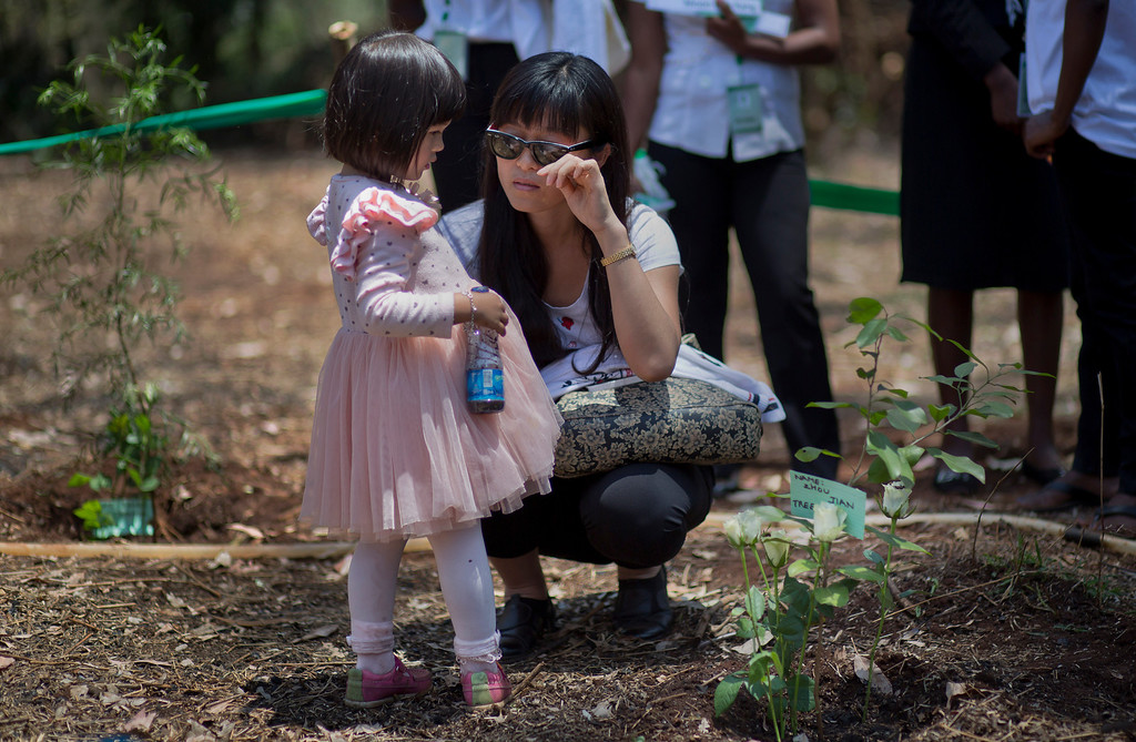 . Wendy Zhang and her daughter Stella, 3, crouch down by the tree she planted in memory of her sister-in-law Zhou Jian who died in the attack, at a memorial service marking the one-month anniversary of the Sept. 21 Westgate Mall terrorist attack, in Karura Forest in Nairobi, Kenya Monday, Oct. 21, 2013. Families and friends of those killed in the attack planted trees in memory of lost loved ones in a ceremony that stressed that the attack occurred against people of all races and religions. (AP Photo/Ben Curtis)