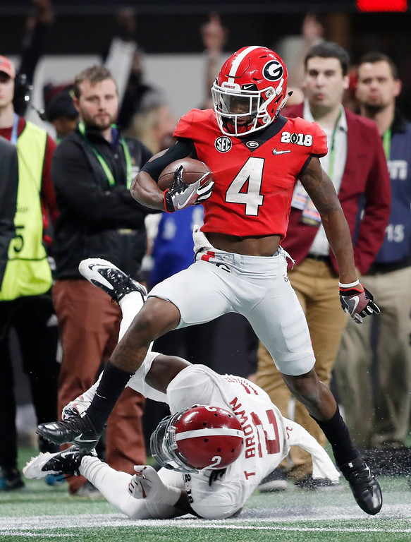 . Georgia wide receiver Mecole Hardmangets past Alabama defensive back Tony Brown for a touchdown catch during the second half of the NCAA college football playoff championship game Monday, Jan. 8, 2018, in Atlanta. (AP Photo/David Goldman)