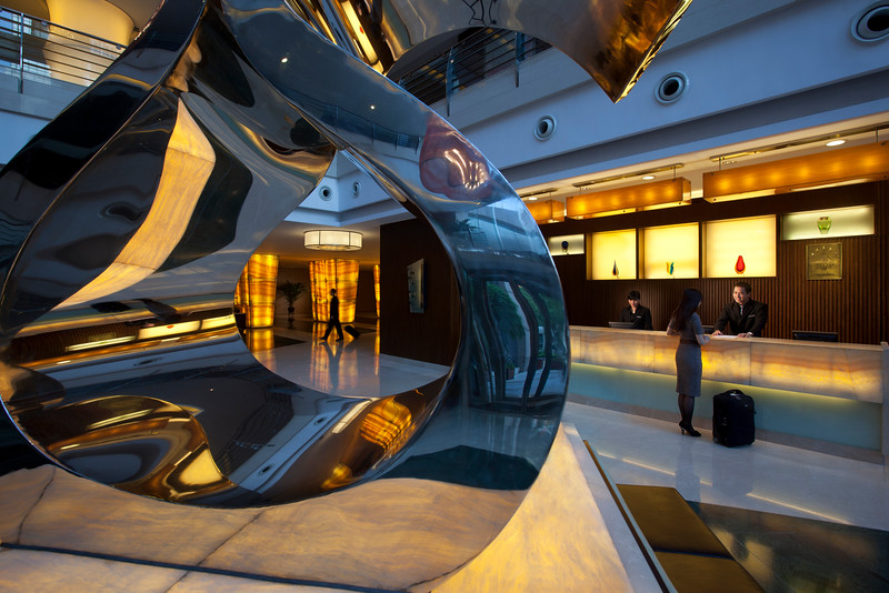 Employees pose at the front desk and lobby of the Marco Polo Shenzhen hotel in Futian District, Shenzhen, Guangdong Province, China.