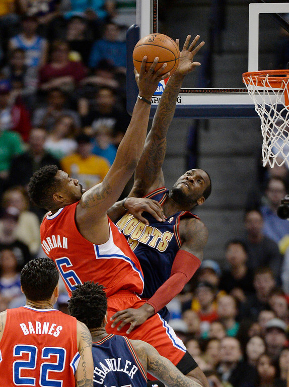 . Los Angeles Clippers center DeAndre Jordan (6) draws the foul on Denver Nuggets center J.J. Hickson (7) as he goes up for a shot during the first quarter. (Photo by John Leyba/The Denver Post)
