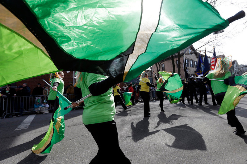 . Women from the Sanford High School color guard, of Sanford, Me., twirl green flags while marching in a St. Patrick\'s Day Parade, in Boston\'s South Boston neighborhood, Sunday, March 17, 2013. (AP Photo/Steven Senne)