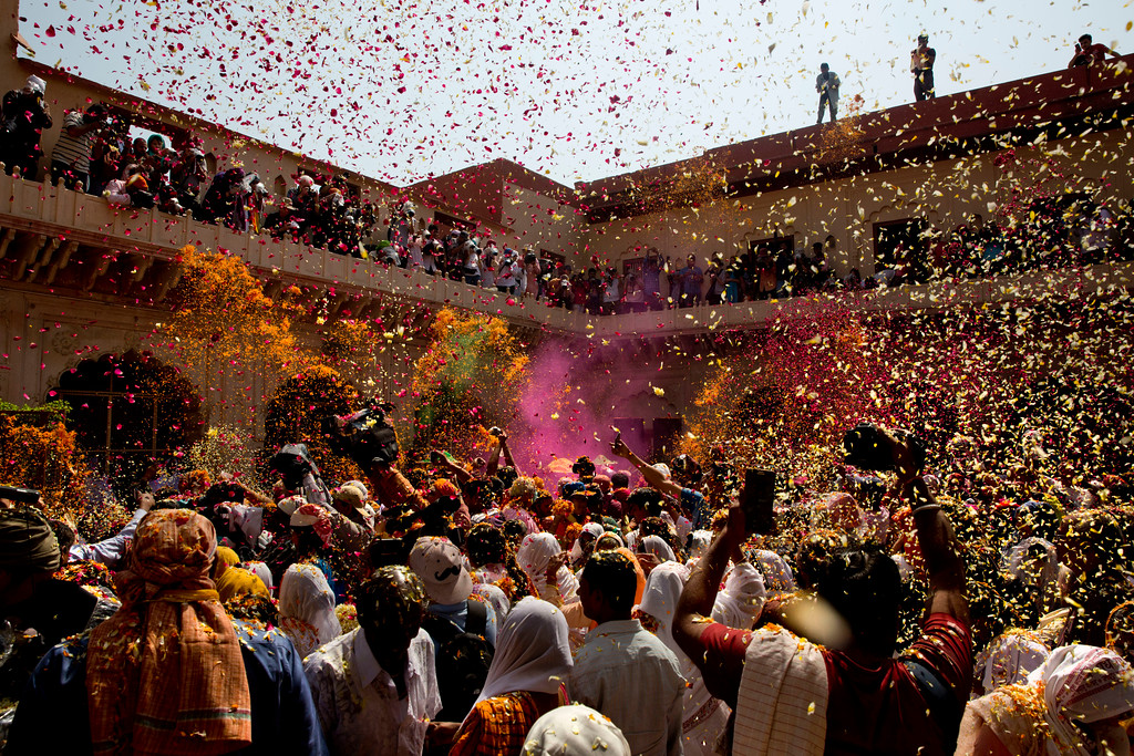 . Locals mixed with Hindu widows, who were once forbidden to participate, throw flower petals and colored powder during the religious arrival of spring festival called Holi at the Gopinath temple in Vrindavan, 180 kilometers (112 miles) south-east of New Delhi, India, Thursday, March 9, 2017. Up to just a few years ago the festival was forbidden for Hindu widows. Like hundreds of thousands of observant Hindu women, they would have been expected to live out their days in quiet worship, dressed only in white, with their very presence being considered inauspicious for all religious festivities. (AP Photo /Manish Swarup)