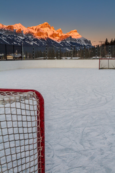 Ice hockey rink in Canmore, Canada with peaks in the background