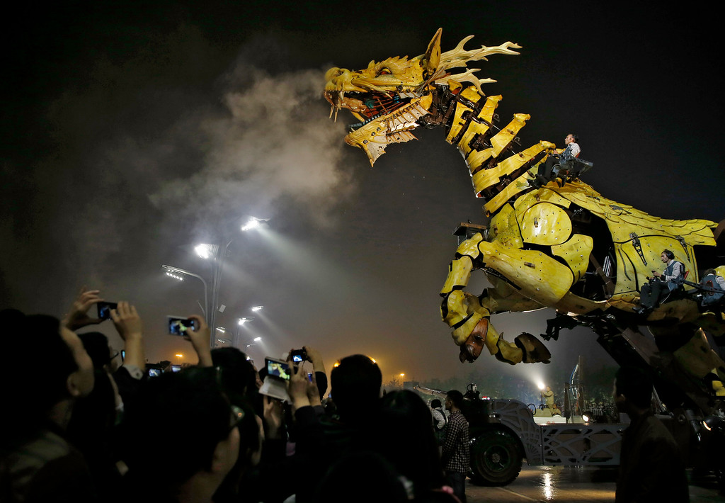 """. People take photos while the French production company La Machine\'s latest creation \""""the Long Ma\"""" or Dragon Horse appears during a performance held in front of the Bird\'s Nest Stadium in Beijing, China Sunday, Oct. 19, 2014. The performance, which attended by French Foreign Minister Laurent Fabius and his Chinese counterpart Wang Yi, mark the climax of celebrations for the 50th anniversary of Sino-French diplomatic relations. (AP Photo/Andy Wong)"""