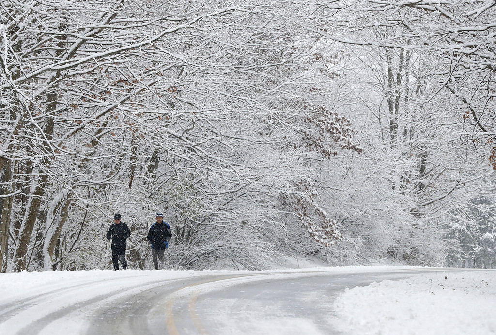 . Ken Perry and Stan Ly go for a run in Eagle Creek Park as snow falls Tuesday, Dec. 13, 2016, in Indianapolis. (AP Photo/Darron Cummings)