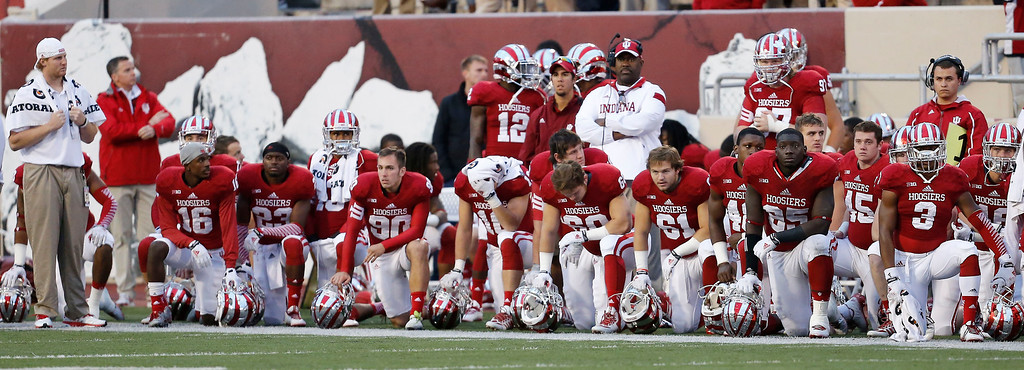 . The Indiana bench watches as Indiana offensive tackle Jason Spriggs (78) is taken off the field on a backboard and cart in the second half of an NCAA college football game in Bloomington, Ind., Saturday, Oct. 18, 2014. Michigan State won the game 56-17. (AP Photo/Sam Riche)