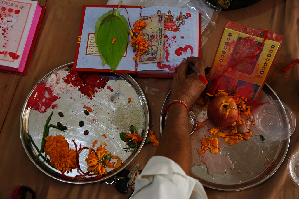 . An Indian businessman performs rituals during Chopada Pujan, or a mass prayer ceremony dedicated to the worship of the account book, on the occasion of Diwali, the Hindu festival of lights, in Ahmadabad, India, Thursday, Oct. 19, 2017. During Chopada Pujan ledgers and new account books are opened by the mercantile community following a special prayer and worship before the idols of Lord Ganesha and Hindu Goddess of wealth Lakshmi to earn their blessings. (AP Photo/Ajit Solanki)